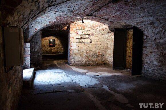 В бывшей тюрьме СД. Свет - только из открытой двери.